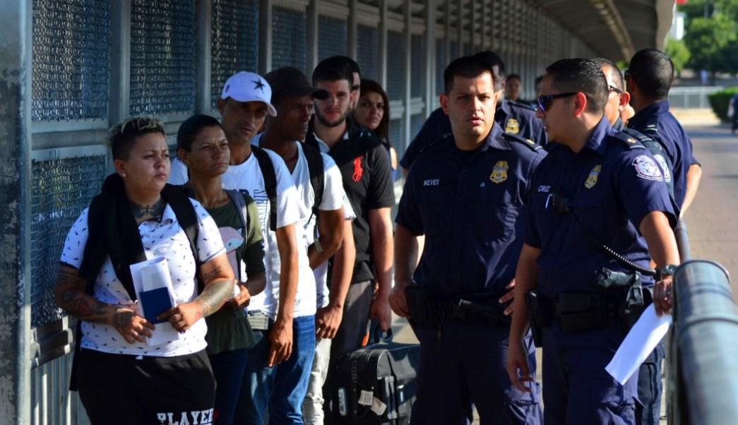 Foto: Funcionarios de EU con migrantes en el puente internacional entre Laredo, Texas y Nuevo Laredo, México, 10 de julio de 2019