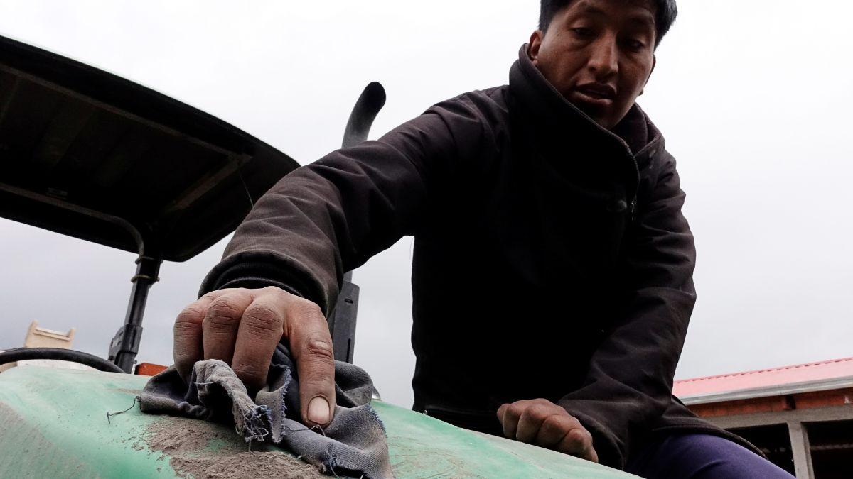 Foto. Un hombre quita la ceniza acumulada en un tractor. El 20 de julio de 2019