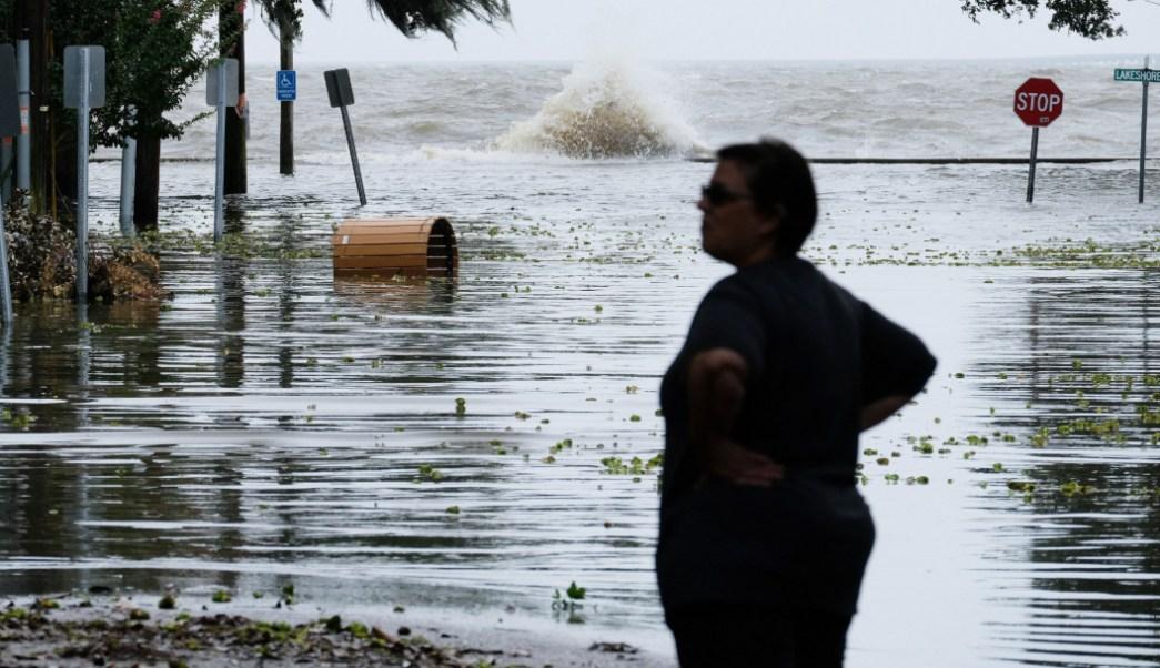 fOTO: Una mujer se para frente a una carretera inundada cerca del lago Una mujer parada frente a una carretera inundada cerca del lago Pontchartrain cuando se aproxima el huracán Barry en Mandeville, Louisiana.