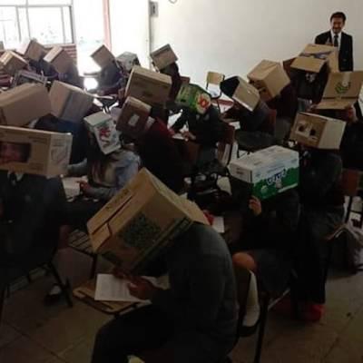 Maestro pone cajas de cartón en la cabeza a alumnos para evitar que copien