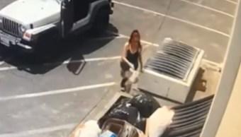 Foto: Una mujer tira a la basura una bolsa con cachorros de perro. YouTube/RivCOanimalsPIO
