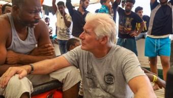 """Foto: Richard Gere habala con un migrante varado en el barco """"Open Arms"""" al frente de la isla italiana de Lampedusa. El 9 de agosto de 2019. AP"""