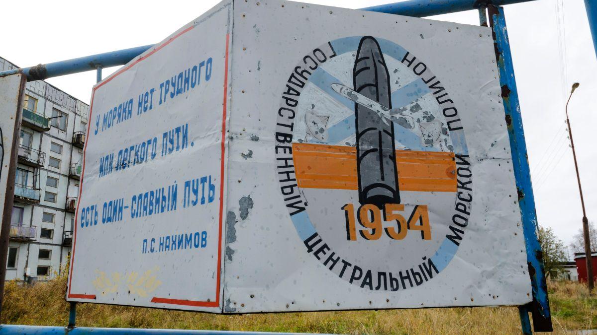 """Foto: Una valla publicitaria que dice """"El campo de pruebas de la Marina Central del Estado"""" cerca de edificios residenciales en la aldea de Nyonoksa, en Rusia. AP/Archivo"""