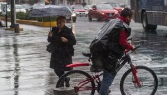 Foto: Una mujer se protege de la lluvia, 24 agosto 2019