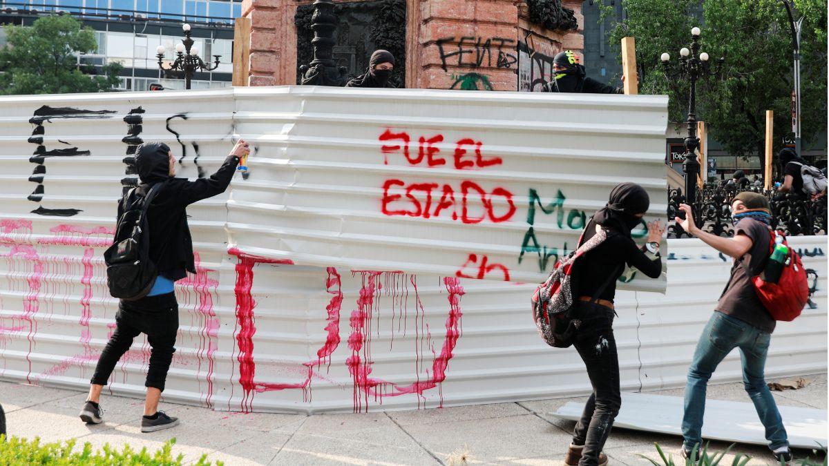 Foto: Encapuchados pintan el monumento en la Glorieta de Colón. Reuters