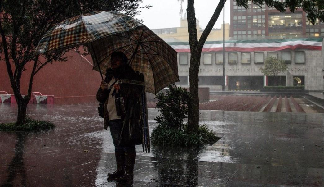 Foto: Una persona se cubre de la lluvia con dos paraguas en la zona centro de la Ciudad de México. Cuartoscuro