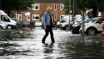 Foto: Una mujer camina por una calle inundada en Battersea, en Londres, Inglaterra. Getty Images/Archivo