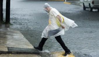 Una persona se protege de la intensa lluvia, 8 septiembre 2019