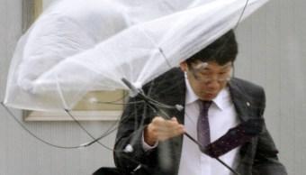 Foto: Un hombre se protege de la lluvia y los fuertes vientos provocados por un tifón, 8 septiembre 2019