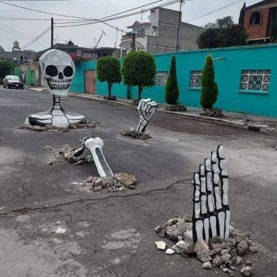 'Simulan' baches y colocan calaveras gigantes en Tláhuac, CDMX