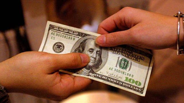 Foto: Dos personas sostienen con su manos un billete de 100 dolares, 21 noviembre 2019