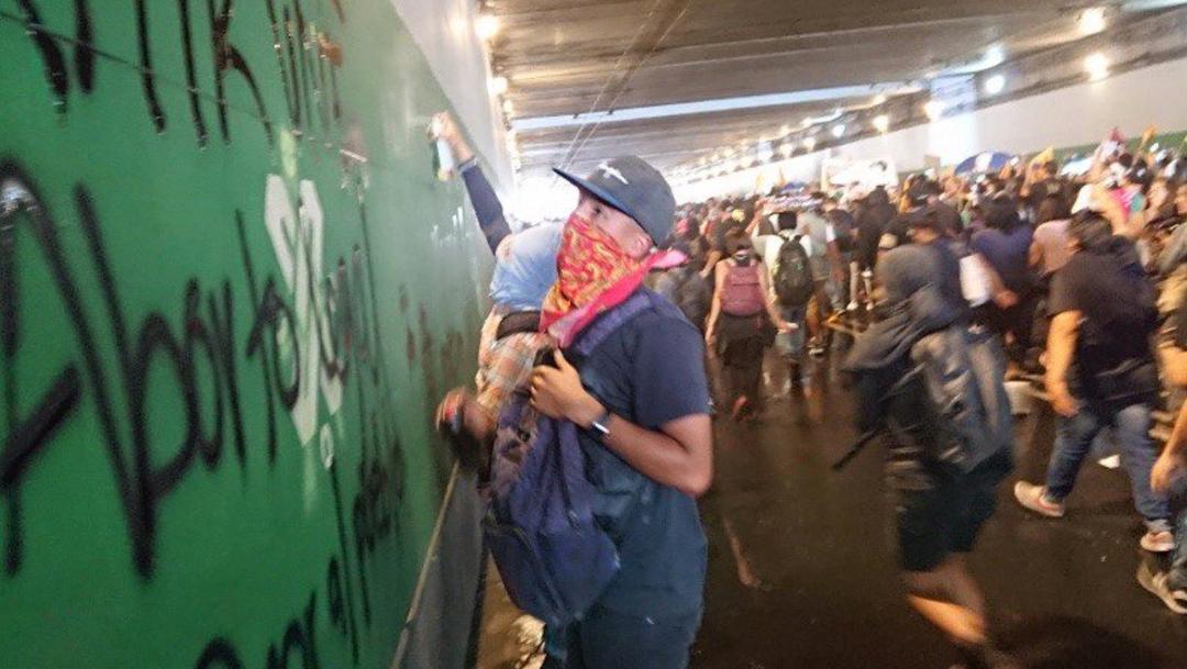 Joven encapuchado realiza pintas en un bajo puente, 02 octubre del 2019 (Twitter @ContraReplicaMX)
