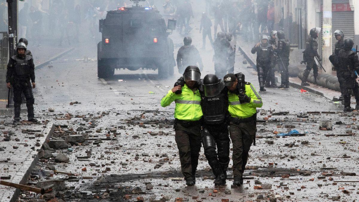 Foto: Dos policías cargan a un compañero herido durante los disturbios. Reuters