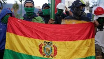Foto: Dos manifestantes cargan una bandera de Bolivia. Reuters