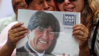 Foto: Dos mujeres sostienen un cartel con la fotografía del expresidente de Bolivia, Evo Morales. Reuters