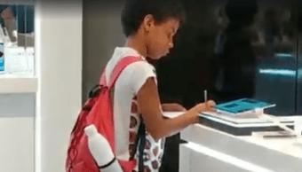 Foto niño usa tablet de exhibición en tienda comercial para hacer su tarea 12 noviembre 2019