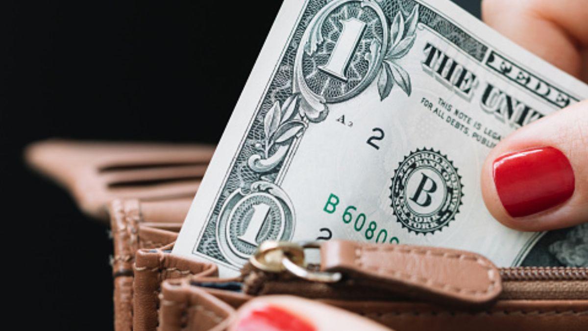 Foto: Una mujer saca un dólar de una cartera. Getty Images