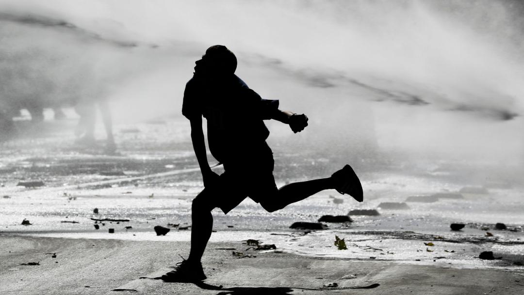 FOTO: Manifestante chileno es rociado por un cañón de agua de la policía, el 28 de diciembre de 2019