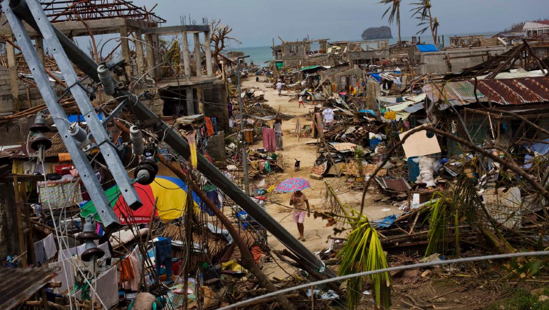 Foto: Sobrevivientes del tifón Haiyan caminan a través de los escombros en el pueblo de Maraboth, Filipinas, 14 noviembre 2019