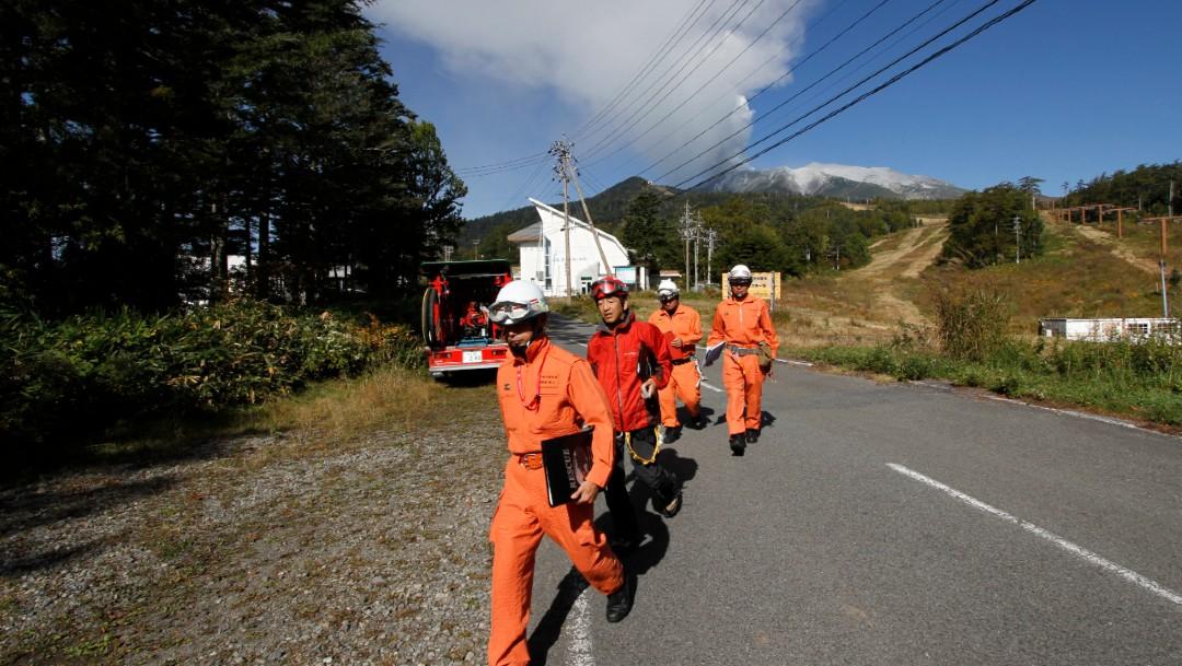 Foto: Los bomberos caminan por una carretera para alejarse del volcán Ontake mientras continúa en erupción, 28 septiembre 2014