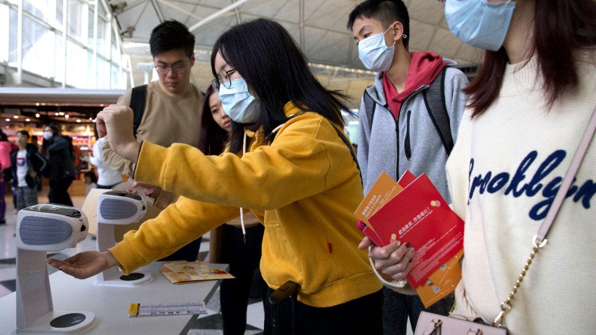 Foto: Viajeros usan gel antibacterial y cubreboca en el Aeropuerto Internacional de Hong Kong. AP