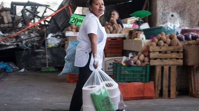 Foto: Una señora carga bolsas de plástico y rollos de papel. Cuartoscuro