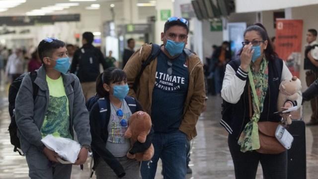 Foto: Una familia usa cubreboca en el Aeropuerto Internacional de la Ciudad de México. Cuartoscuro