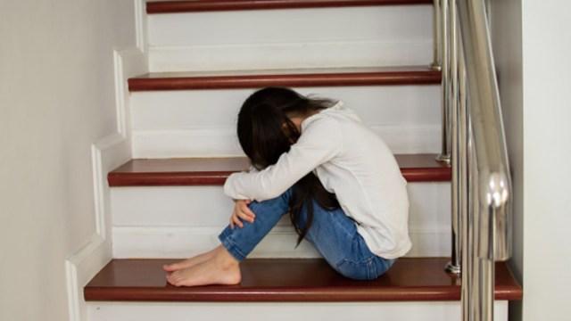 Foto: Una niña sentada en las escaleras se cubre el rostro. Getty Images/Archivo