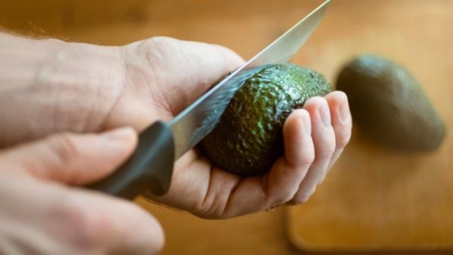 Una persona cortando aguacate.