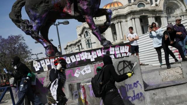 Foto: Mujeres encapuchadas realizan pintas durante la marcha del #8M, 08 de marzo de 2020, (Reuters)