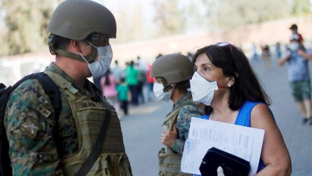 Foto: Una mujer conversa con un militar en Santiago de Chile durante la crisis por COVID-19, 22 marzo 2020
