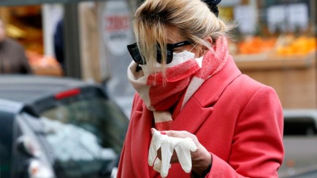 Foto: Una mujer camina por calles de París con el rostro cubierto por coronavirus. Getty Images