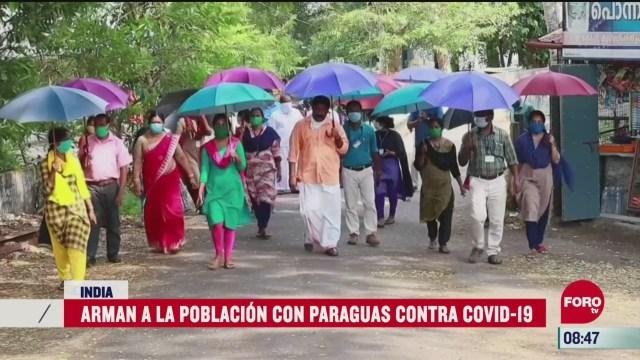 en india guardan la sana distancia con paraguas