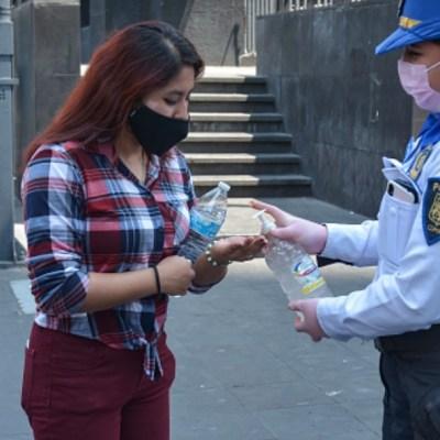 Foto: Una policía ofrece gel antibacterial en calles de la CDMX. Getty Images