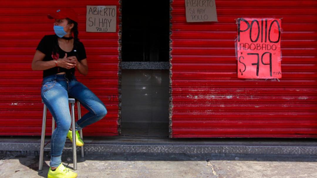 Foto: Una joven sentada a la espera de clientes en una pollería. Getty Images