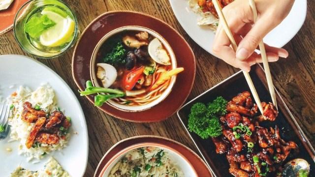 comida-en-diversos-platillos-con-una-mano-tomando-carne-con-palillos-buffet