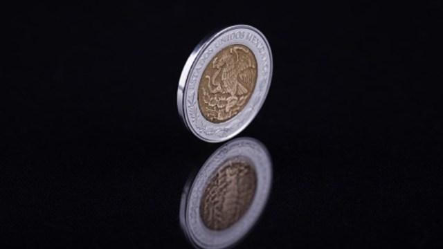 Una moneda de un peso mexicano rodando en un fondo negro. Getty Images