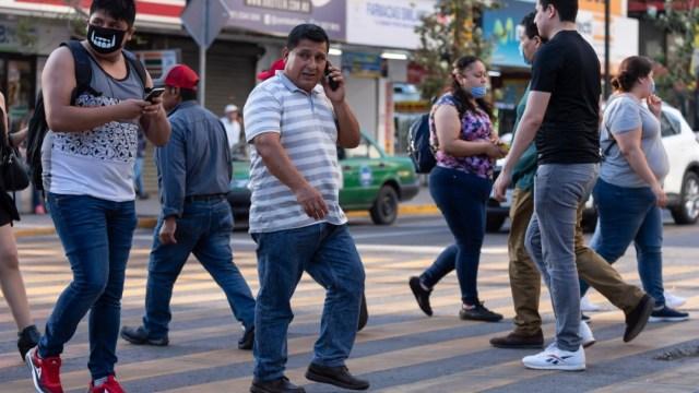 Personas con y sin cubrebocas caminan por una calle de Nuevo León. Getty Images