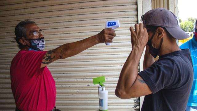 hombre con termometro infrarrojo tomando temperatura a otro