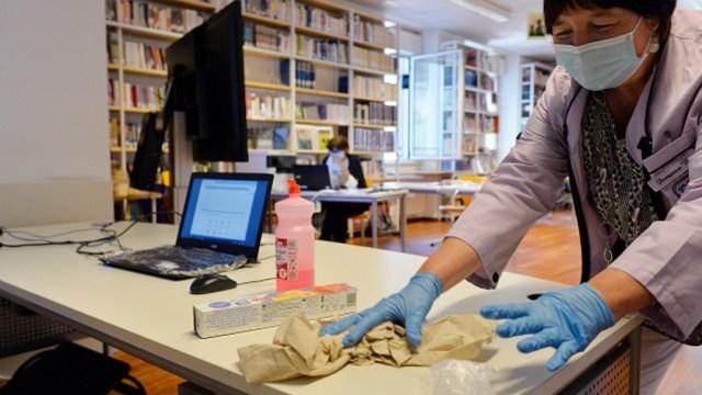 Mujer desinfecta muebles en una escuela de Italia por coronavirus