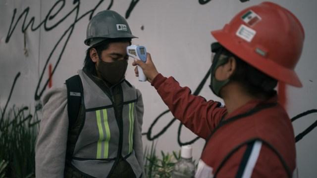 Toman la temperatura a trabajadores. Getty Images
