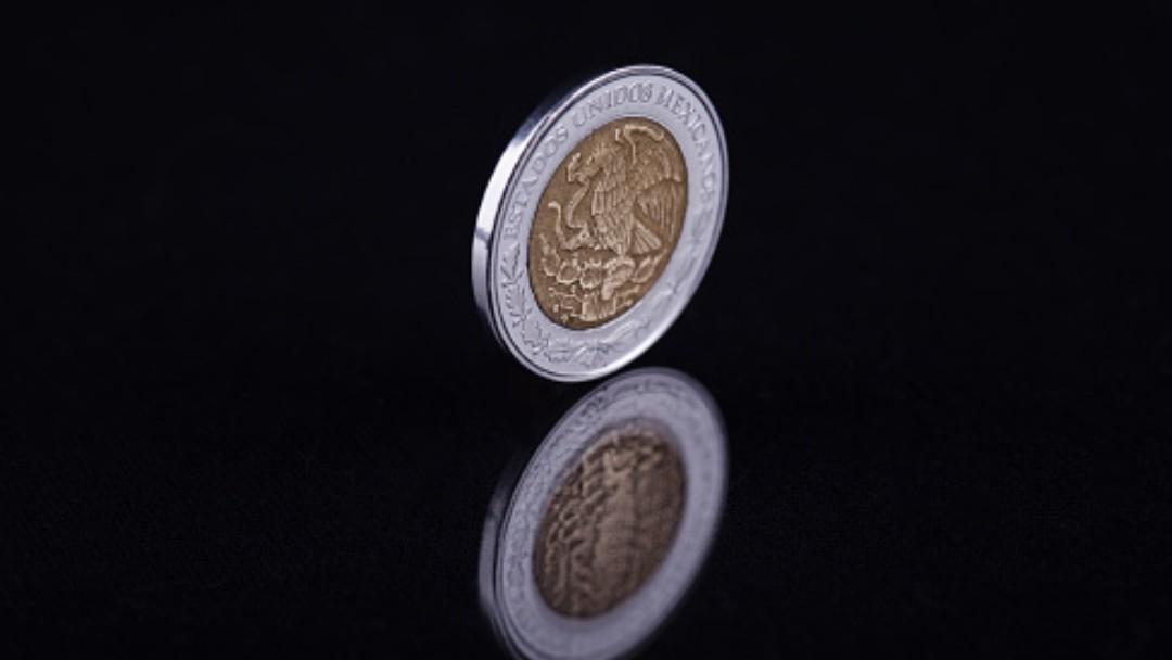 Moneda de un peso mexicano rueda en una mesa. Getty Images