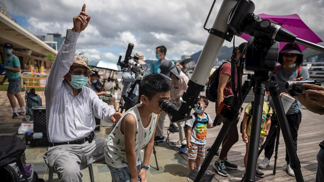 Un joven mira a través del telescopio de un astrónomo aficionado durante un eclipse de sol en Hong Kong, China. (Foto: EFE)