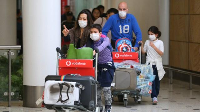 Personas con cubrebocas en el aeropuerto; OMS recomienda a viajeros estar atentos al COVID-19 en 'cualquier parte'