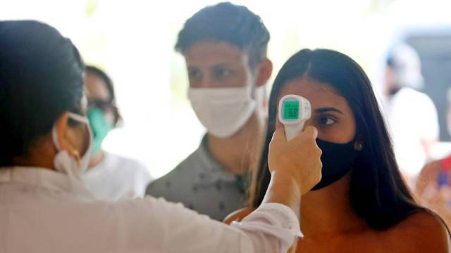Una trabajadora de la salud toma la temperatura a visitantes del Hotel Meliá Sol Palmeras de Varadero, en Cuba
