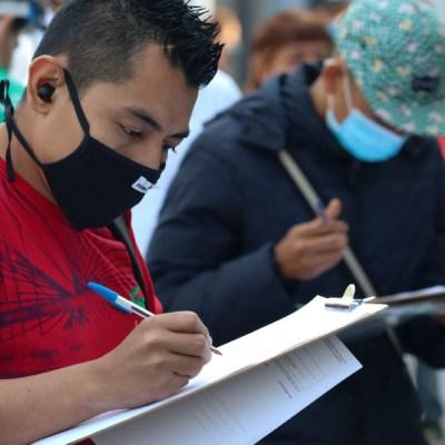 Un grupo de personas llenan solicitudes de empleo