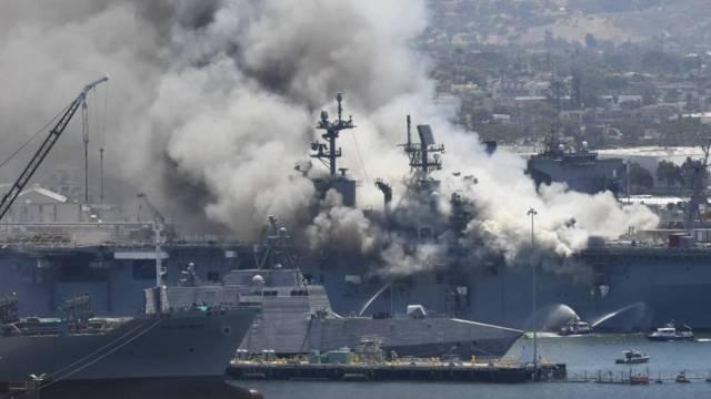 Una enorme columna de humo se eleva sobre el buque USS Bonhomme Richard en la base naval de San Diego el domingo 12 de julio de 2020 tras un incendio y explosión a bordo