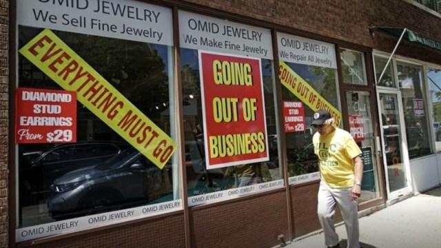 Un hombre camina frente a joyería cerrada en Estados Unidos; baja en junio el índice de desempleo