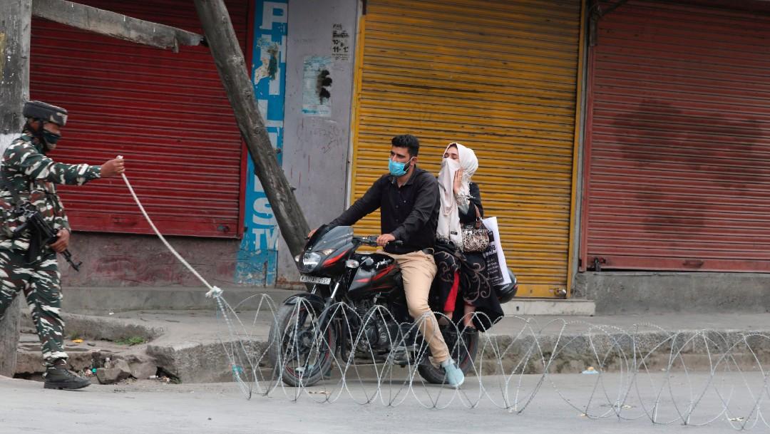 Un soldado abre paso a una pareja en motocicleta en India