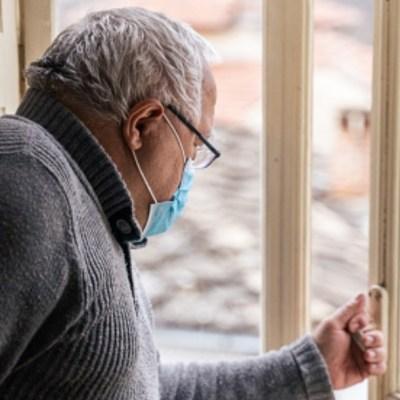 Un abuelito usa cubrebocas mientras ve por la ventana
